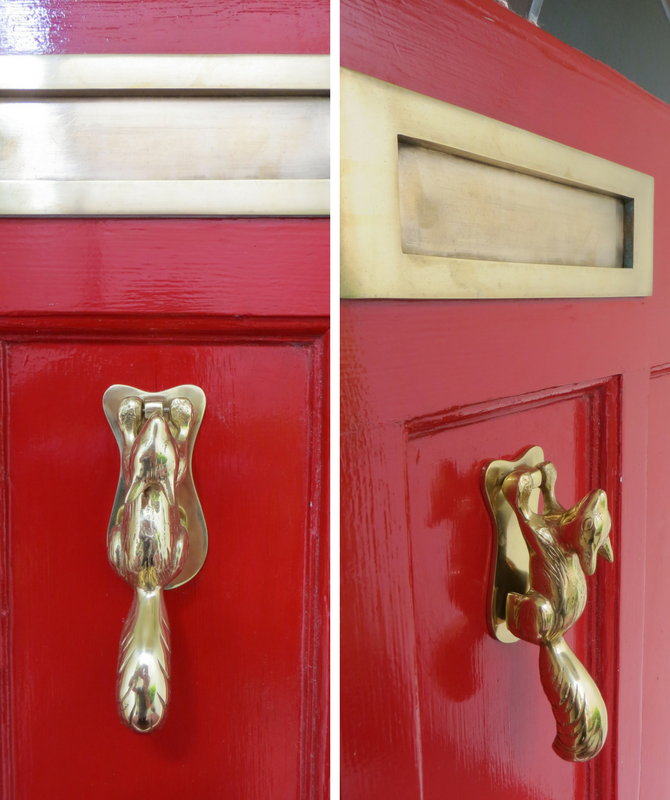 Brass squirrel door knocker on a red front door