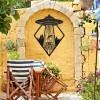 """Get in Loser"" Alien Wall Art on a Yellow Brick Wall in the Garden"