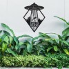 """""""I Want to Believe""""Alien Wall Art in Situ Above Bushes in the Garden"""