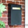 Black and Brass Newspaper Box On Brick Wall