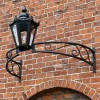 Black bow bracket with black lantern above archway on brick wall