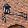 Black bow bracket with black lantern above archway on brick wall