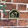 Vinyl Black & Brass Arched Number Sign in situ on the Frpont of a House