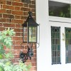Black Victorian Wall Light With Brass Bar Decoration Installed Outside Porch