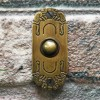 Art Nouveau inspired door bell on brick wall