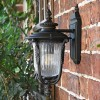 """Side View of the """"Christleton"""" Bronze Wall Mounted Porch Light Mounted on a Brick Wall"""