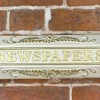 Close Up of Lettering on Cream Newspaper Holder