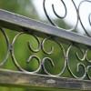 Detailed image of ornate scroll work on garden swing seat