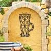 Geometric Steel Latte Glass Wall Art on a Yellow Garden Wall