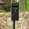King George Rex Black Period Post Box by a Stone Wall