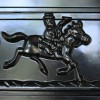 Detailed image of man riding horse on front of letter box door