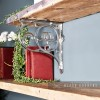 """Lotus Flower"" Bright Chrome Wall Bracket Holding up a Wooden Shelf"