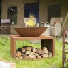 Rustic Fire Bowl in Use with Logs in the Log Store