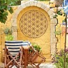 "Geometry ""Flower of Life"" Steel Wall Art in a Display in the Garden on a Yellow Wall"