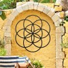 """Black """"Seed of Life"""" Steel Wall Art on a Yellow Garden Wall"""
