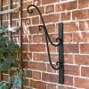 Black Scrolled Hanging Basket Bracket in Situ on a Black Wall