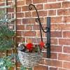Black Scrolled Hanging Basket Bracket Holding a Flower Basket in the Garden