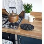 Black oval heavy duty trivet in kitchen