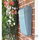 Modern letter box on wall in garden