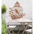 Bird Cage Wall Art in the Garden Above a Wooden Table & Chair Set