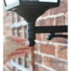 Black outdoor traditional wall lamp close up of bracket attachment