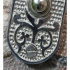 Close up of ornate pattern on door push button