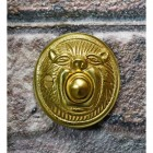 Polished brass bell push on brick wall