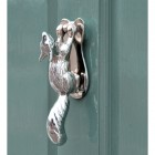Squirrel door knocker finished in chrome on blue, green door