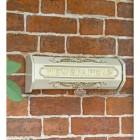 Cream Newspaper Holder Mounted On Brick Wall