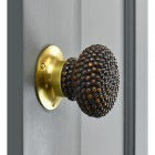 Brown Studded door knob with polished brass backplate on grey door