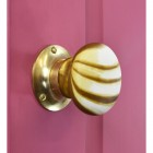 Stone Effect door knob on pink door with polished brass backplate