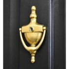 Polished Brass Urn door knocker with security viewer on black door