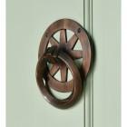 Antique copper wheel spoke door knocker on green door