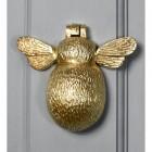 Polished brass bumblebee door knocker on grey door