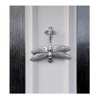 Bright chrome Dragon fly door knocker on white door