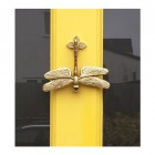 Dragon Fly Door Knocker finished in Polished Brass, mounted on yellow door.