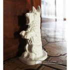 "White Cast Iron ""Digby"" Dog Door Stop Next to a Brown Door"
