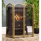 4 fold polished brass fireguard in fornt of log burner