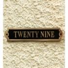 The Number Twenty Nine Displayed on the Black & Brass Gate Number Sign