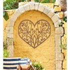 Flower Foliage Heart Wall Art in Situ in on a Yellow Garden Wall