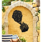 Floating House on Balloons Steel Wall Art on a Yellow Brick Wall in a Garden
