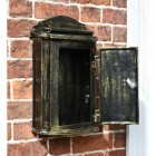 Post box mounted on wall with door open