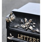 Close up of floral and rose detailing on post box