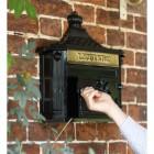 Man using key to open post box door