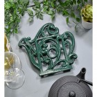 Green Cast Iron Kettle Trivet in Situ on Blue Table