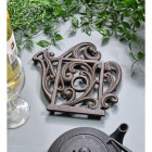 Rustic Kettle Shaped Cast Iron Trivet in Situ on Blue Table