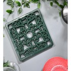 Green Square Cast Iron Trivet in Situ on Grey Surface