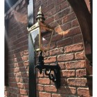 Polished Brass Harrogate Wall Lantern on Bracket Mounted on a Brick Wall in the Garden