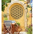 """Geometry """"Flower of Life"""" Steel Wall Art in a Display in the Garden on a Yellow Wall"""