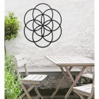 "Black ""Seed of Life"" Steel Wall Art in Situ Outdoors by a Wooden Table and Chairs Set"